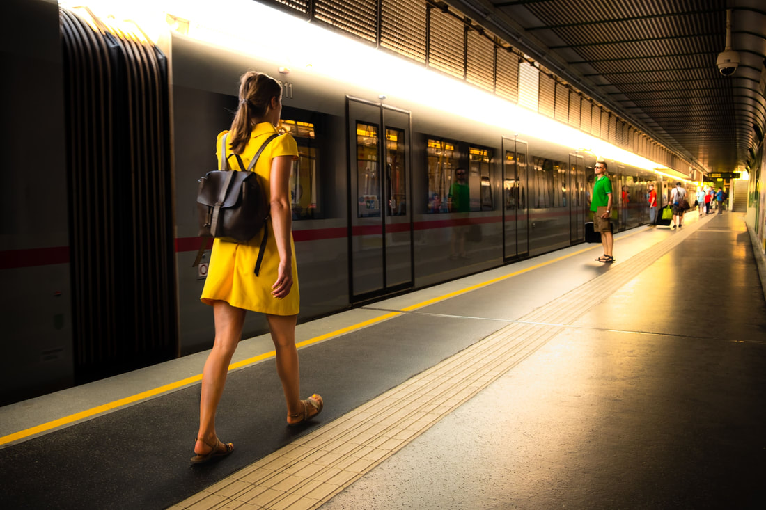 A woman in a yellow dress at the train station approaches a train